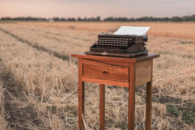 Machine à écrire sur une table de chevet en noyer dans un champ de blé au coucher du soleil Photo Premium