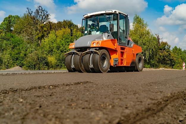 Les machines de construction pour les travaux routiers traversent un nouvel asphalte en été des arbres Photo Premium