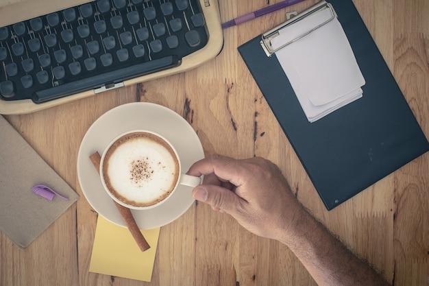 Machines à écrire vintage et tasse de café sur la table en bois. Photo Premium