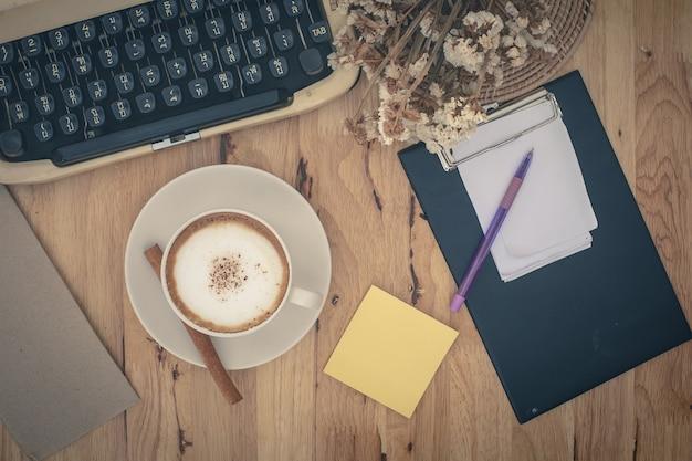 Machines à écrire vintage et tasse de café sur la table en bois Photo Premium