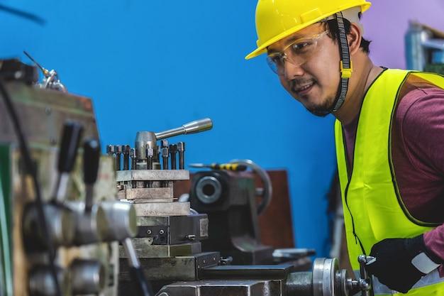 Machiniste asiatique en combinaison de sécurité, actionnant les tours professionnels dans une usine de travail des métaux Photo Premium
