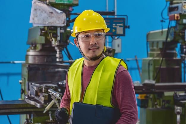 Une machiniste asiatique en combinaison de sécurité vérifie la liste des tâches avec du papier-cahier des charges Photo Premium