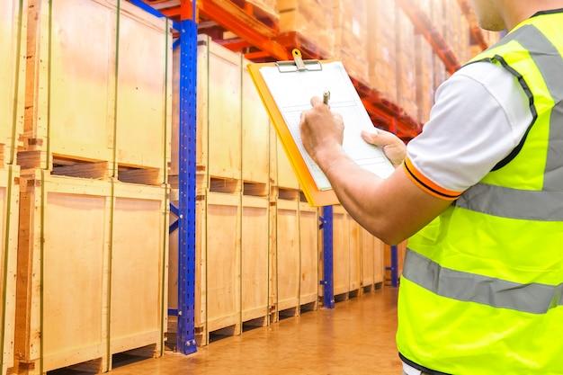 Magasinier tenant presse-papiers inspectant des produits sur des étagères hautes dans un entrepôt de stockage Photo Premium