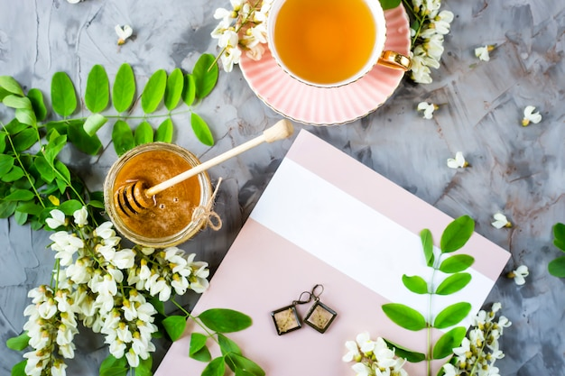 Le magazine à côté d'une tasse de thé et d'un pot de miel Photo Premium