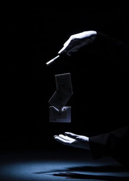 Magicien effectuant un tour avec une baguette magique sur fond noir Photo gratuit