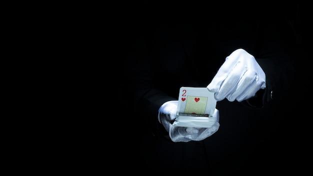 Magicien effectuant un tour avec des cartes à jouer sur fond noir Photo gratuit