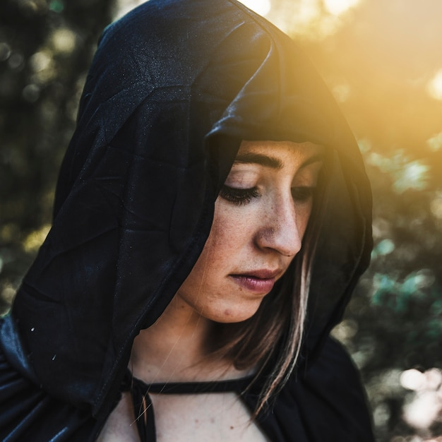 Magicien femelle en cape noire dans la forêt ensoleillée Photo gratuit
