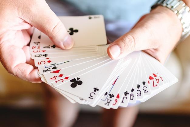 Magicien mains faisant tour de magie avec des cartes à jouer. Photo Premium