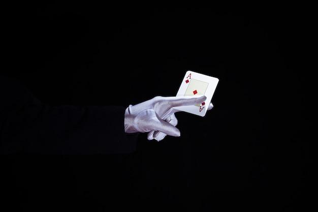 Magicien, tenue, aces, jouer carte, dans, doigts, sur, arrière-plan noir Photo gratuit