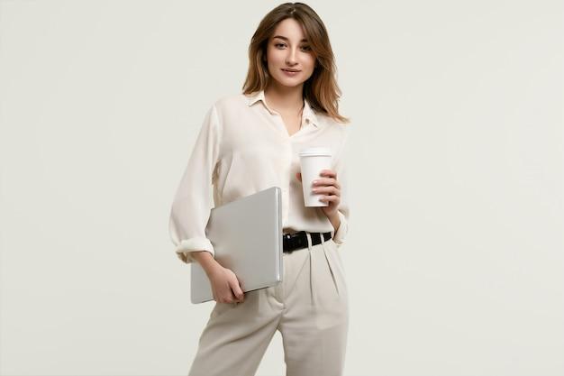 Magnifique modèle brune en vêtements blancs avec ordinateur portable et café Photo Premium