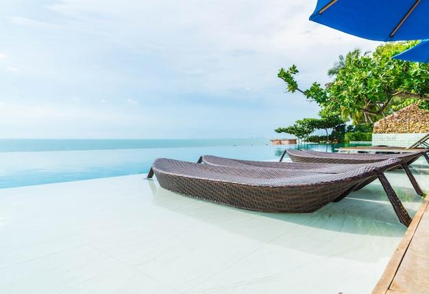 Magnifique parasol et chaise de luxe autour de la piscine extérieure de l'hôtel et de la station Photo Premium