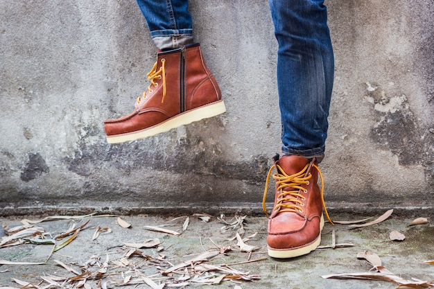 Maie foot avec des chaussures en cuir marron et un jean Photo gratuit