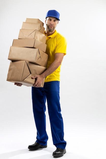 Mailman Brésilien Sur Fond Blanc La Livraison D'un Colis. Copie Espace. Photo Premium