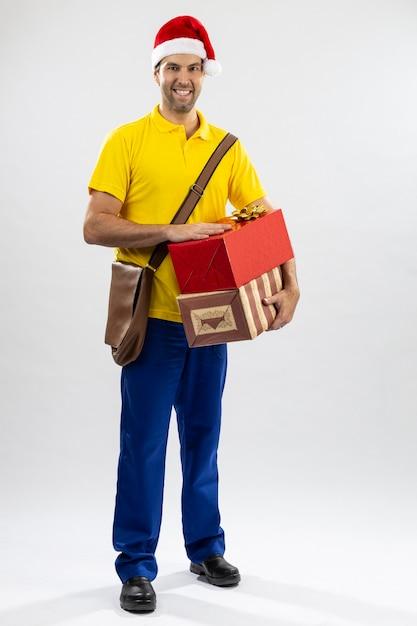 Mailman Brésilien Habillé En Père Noël Offrant Un Cadeau Sur Un Fond Blanc. Copie Espace. Photo Premium