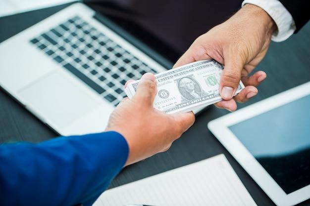 Main d'affaires donnant de l'argent espace de travail dans le bureau- dollars des états-unis (ou usd) Photo Premium