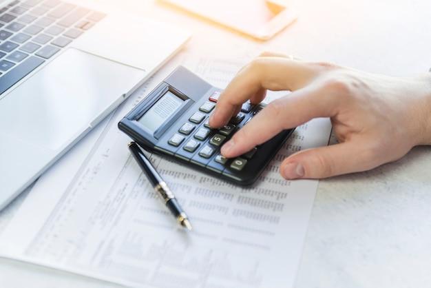 Main à l'aide d'une calculatrice analysant la table sur papier Photo gratuit
