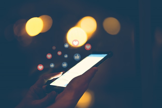 Main à l'aide de téléphone intelligent avec le concept de médias sociaux. Photo Premium