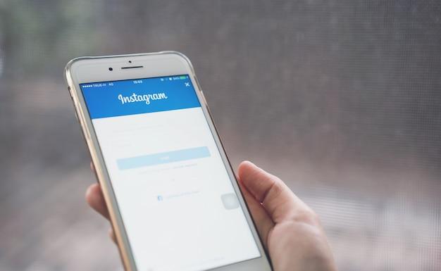 Main appuie sur l'icône instagram de l'écran de connexion Photo Premium
