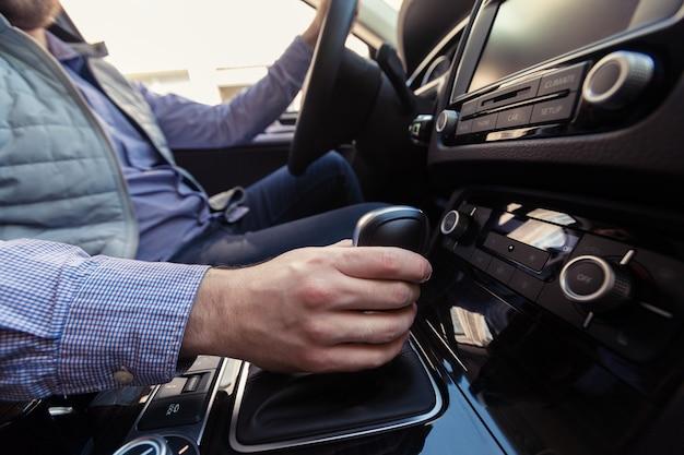 Main en appuyant sur le bouton d'alimentation pour allumer le système stéréo de la voiture Photo Premium