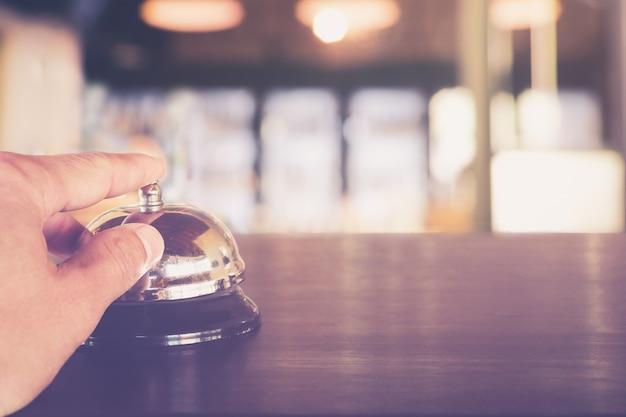 Main En Appuyant Sur Un Service D'appel De Service Sur Le Comptoir De La Réception De L'hôtel Se Bouchent Photo Premium