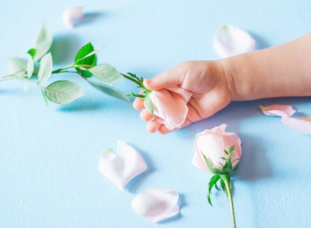 Main d'art de mode d'un petit enfant tenant des fleurs sur fond bleu Photo Premium