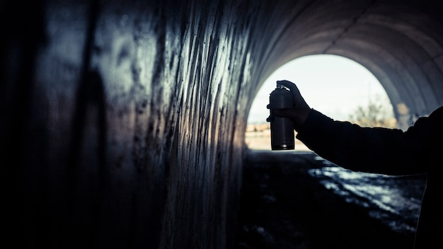 Main de l'artiste peinture graffiti avec aérosol à l'intérieur du tunnel Photo gratuit