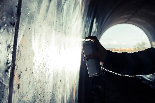 Main de l'artiste peinture graffiti avec aérosol sur le mur Photo gratuit