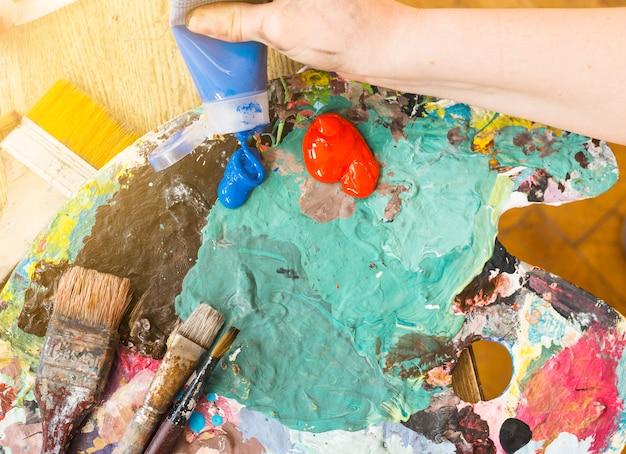 Main d'artiste pressant un tube de peinture à l'huile bleue sur une palette en désordre Photo gratuit