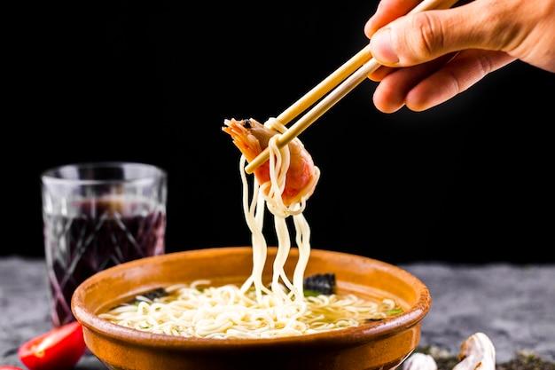 Main avec des baguettes tenant des nouilles aux crevettes Photo gratuit