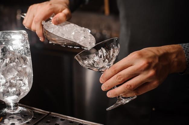 Main de barman mettant la glace dans le verre à cocktail Photo Premium
