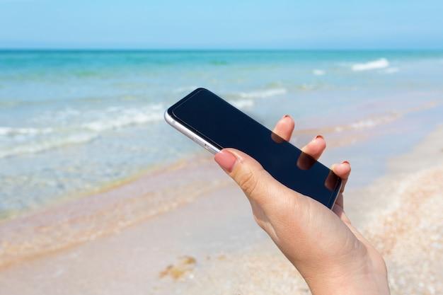 Main De Belle Femme à L'aide D'un Téléphone Intelligent Sur La Plage Photo Premium