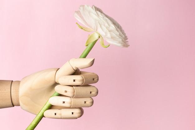 Main En Bois Avec Une Fleur Blanche Sur Un Rose Photo Premium