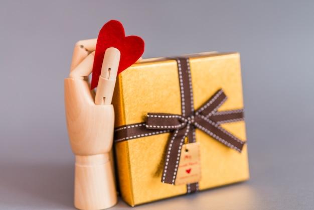Main en bois tenant coeur rouge près de boîte-cadeau Photo gratuit