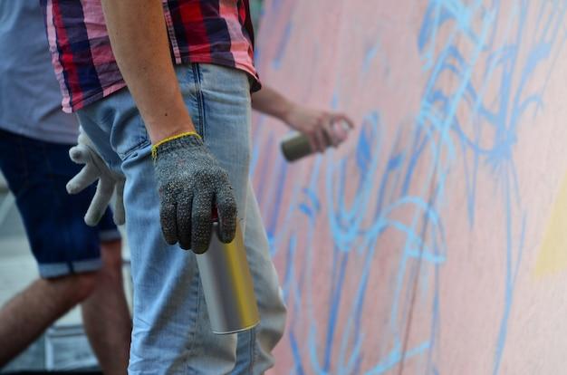 Une main avec une bombe aérosol qui dessine un nouveau graffiti sur le mur Photo Premium