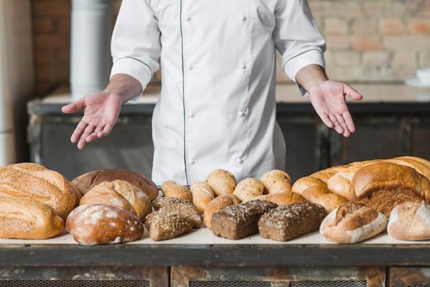 Main de boulanger montrant divers pains cuits Photo gratuit