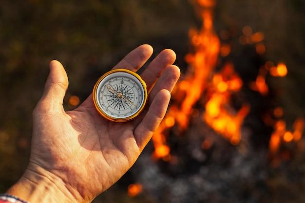Main avec boussole et flammes de feu le long Photo gratuit