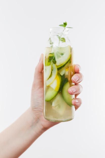 Main avec une bouteille de limonade aux fruits Photo gratuit