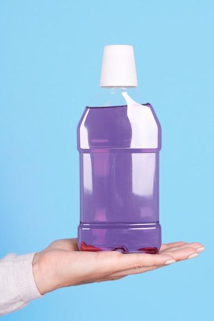 Main Avec Bouteille De Rince-bouche Violet Isolé Photo Premium
