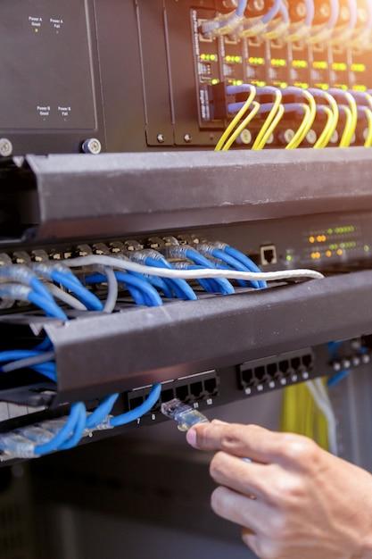 Main avec des câbles réseau connectés aux serveurs dans un centre de données Photo Premium