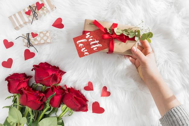 Main avec cadeau avec étiquette près de coeurs d'ornement et de fleurs fraîches sur une couverture en laine Photo gratuit