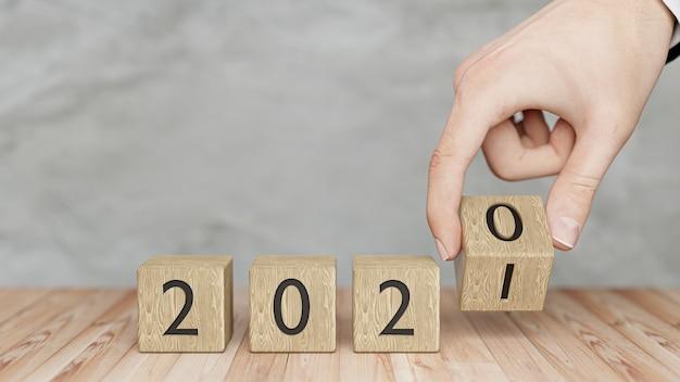 Main Change Le Cube En Bois De 2020 à 2021. Bonne Année 2021. Rendu 3d. Photo Premium