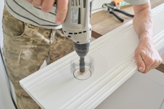 Main de charpentier à l'aide d'outils électriques à bois professionnels Photo Premium