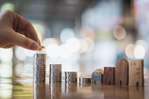Main en choisissant la ligne de monnaie sur la table en bois et mini maison en bois, Photo Premium