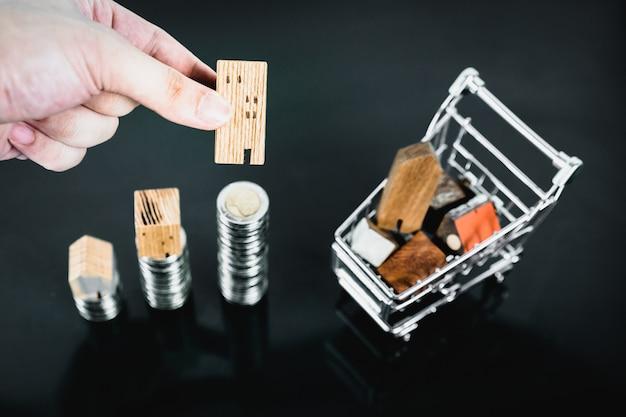 Main en choisissant mini maison en bois de rangée de pièces de monnaie avec chariot sur table noire Photo Premium