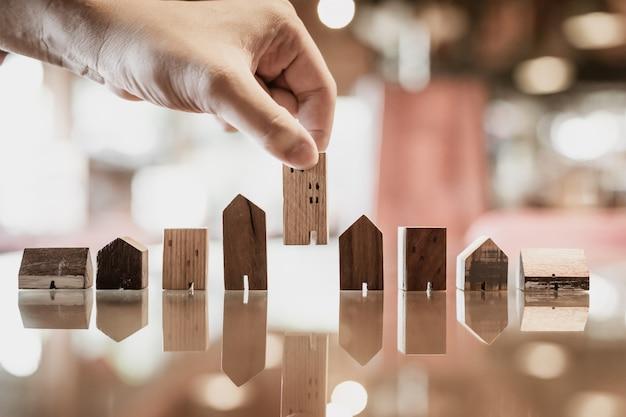 Main en choisissant mini modèle de maison en bois de modèle sur table en bois Photo Premium