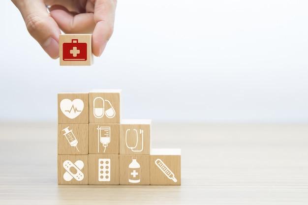 Main, choisissez des icônes de sac de premiers secours sur bloc en bois. Photo Premium