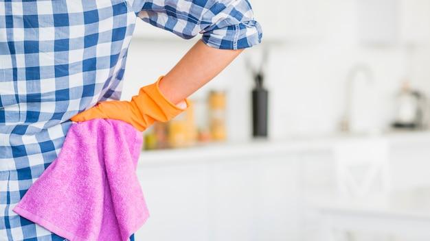 Main de concierge sur la hanche tenant une serviette rose Photo gratuit