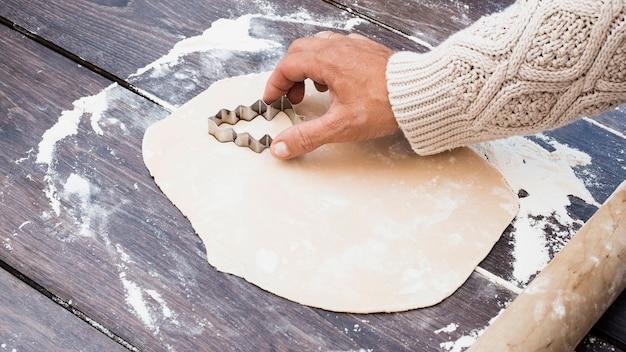 Main coupant des biscuits en forme d'arbre de noël Photo gratuit
