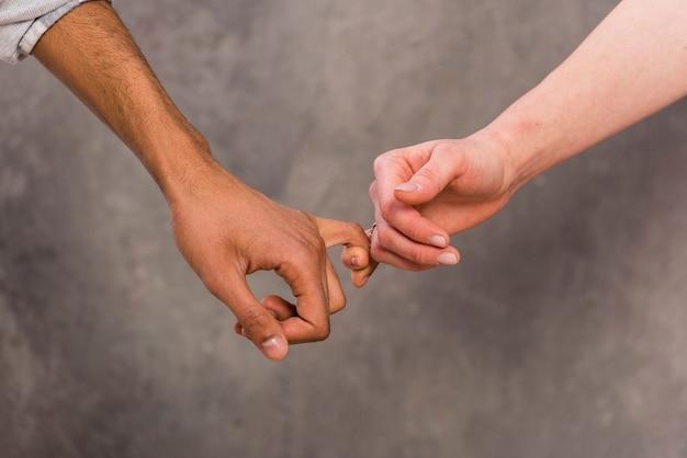 La main d'un couple interracial tenant le doigt de l'autre sur un fond de béton Photo gratuit
