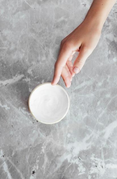 Main et crème sur fond de marbre Photo gratuit